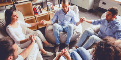group of friend praying while holding their hands