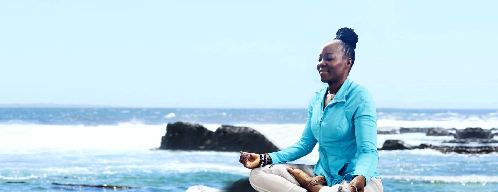 woman is relaxing meditate at the beach while smiling
